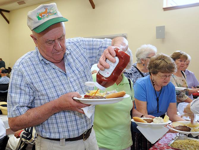 Dave Casic of Canterbury topped off his burger while enjoying a BBQ Social at the Centennial Senior Center.
